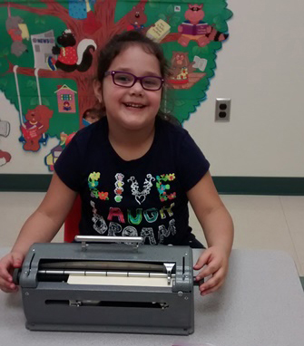 student using braille typewriter