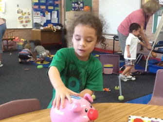 girl playing with pink piggy bank