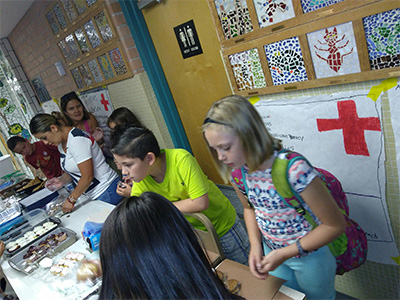 Gale students running a bake sale for hurricane relief.