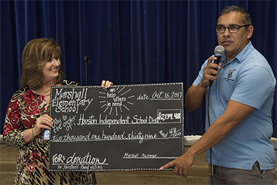 Marshall principal Christopher Loya with Martha Damek presenting the check for Houston Independent School District