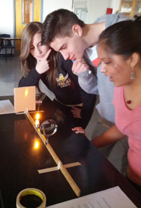 three students observing a science experiment