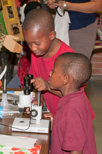 two male students looking at a microscope