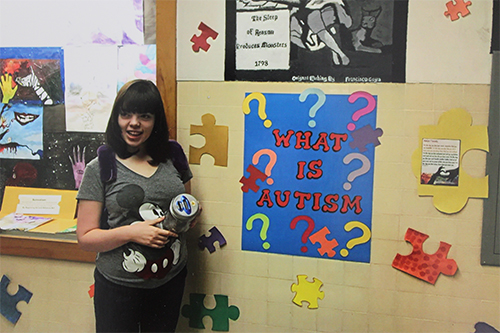 A Palo Verde student smiles next to an autism awareness poster.